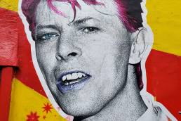 Street art of David Bowie with pink hair on red and yellow striped wall